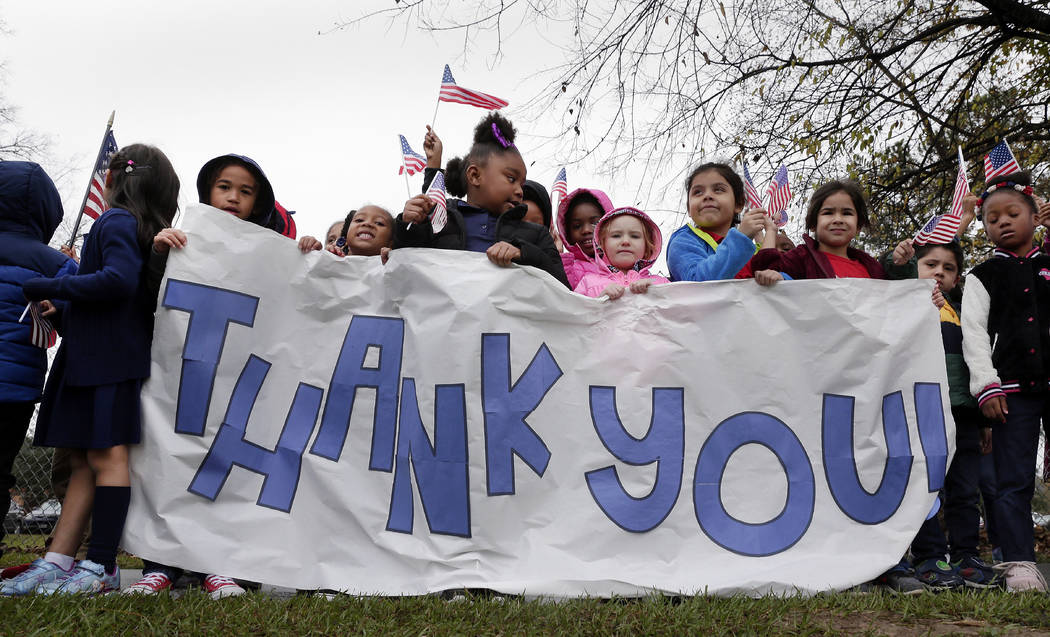 Students from Salyer Elementary School wave flags and signs as the train carrying the body of former president George H.W. Bush travels past their school on the way to Bush's final internment Thur ...