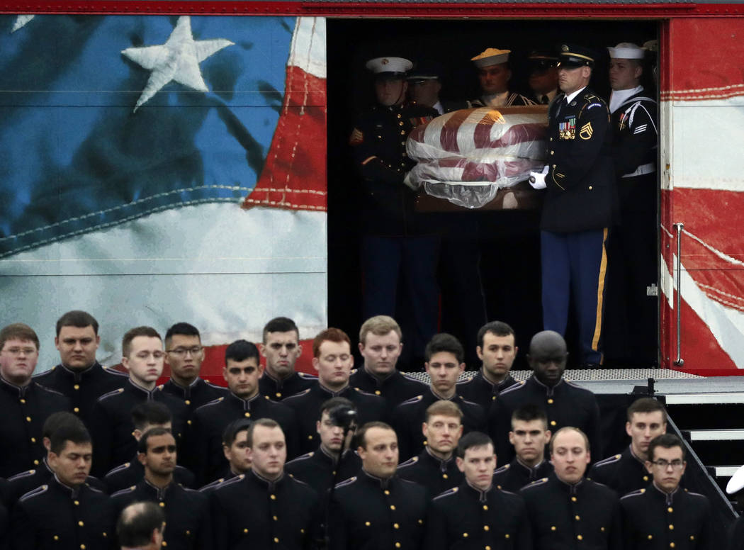 The flag-draped casket of former President George H.W. Bush is carried by a joint services military honor guard after if arrived by train , Thursday, Dec. 6, 2018, in College Station. (AP Photo/Er ...
