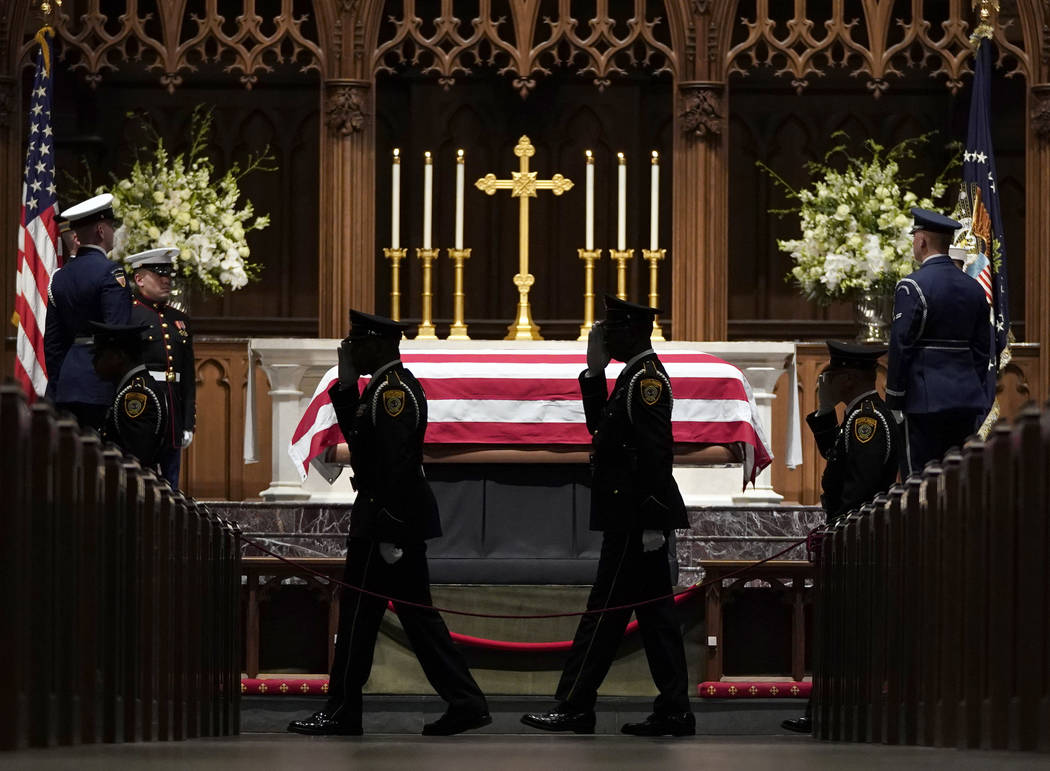 Military members salute as they pay their respects as former President George H.W. Bush lies in repose at St. Martin's Episcopal Church Wednesday, Dec. 5, 2018, in Houston. (AP Photo/David J. Phil ...