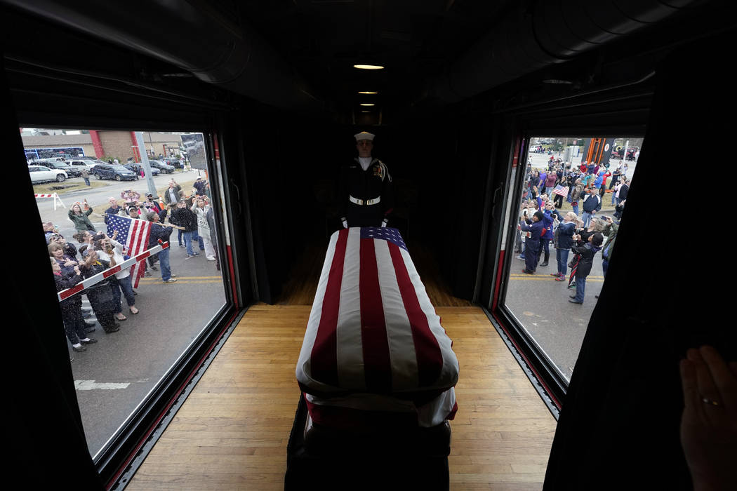 The flag-draped casket of former President George H.W. Bush passes through Magnolia, Texas, Thursday, Dec. 6, 2018, along the train route from Spring to College Station, Texas. (AP Photo/David J. ...