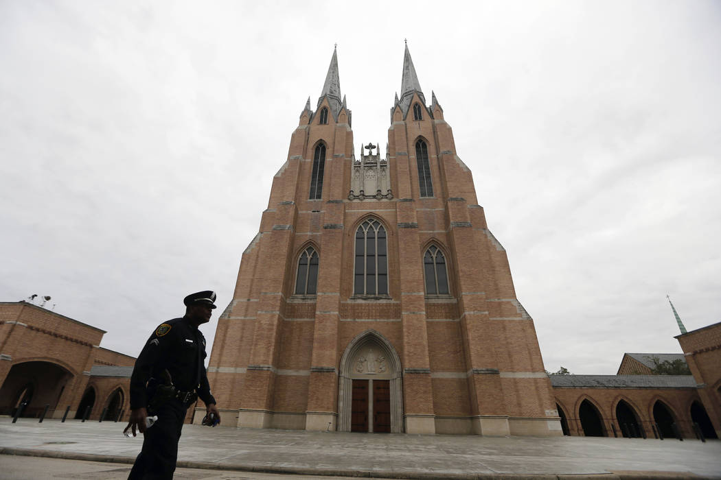 A police officer walks outside St. Martin's Episcopal Church before the funeral for former President George H.W. Bush Thursday, Dec. 6, 2018, in Houston. (AP Photo/Gerald Herbert)