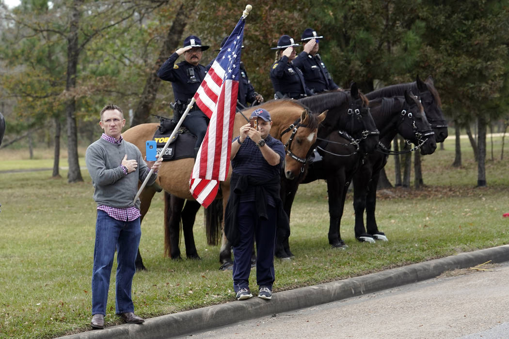 People line the road as the hearse carrying the flag-draped casket of former President George H.W. Bush heads to the Union Pacific train facility Thursday, Dec. 6, 2018, in Houston. (AP Photo/Davi ...