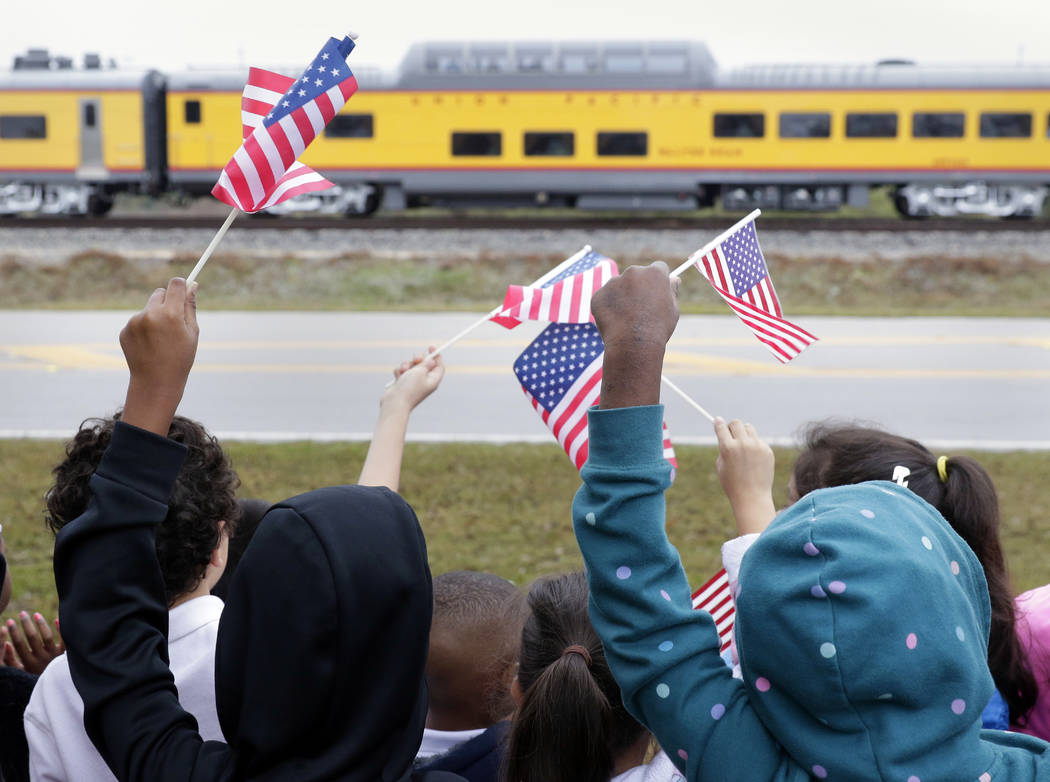 Students from Salyer Elementary School wave flags as the train carrying the body of former president George H.W. Bush travels past their school on the way to Bush's final internment Thursday, Dec. ...
