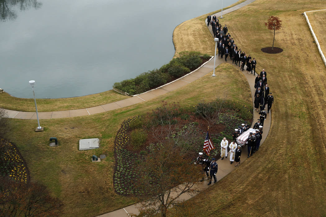 The flag-draped casket of former President George H.W. Bush is carried by a joint services military honor guard followed by family members for burial at the George H.W. Bush Presidential Library a ...