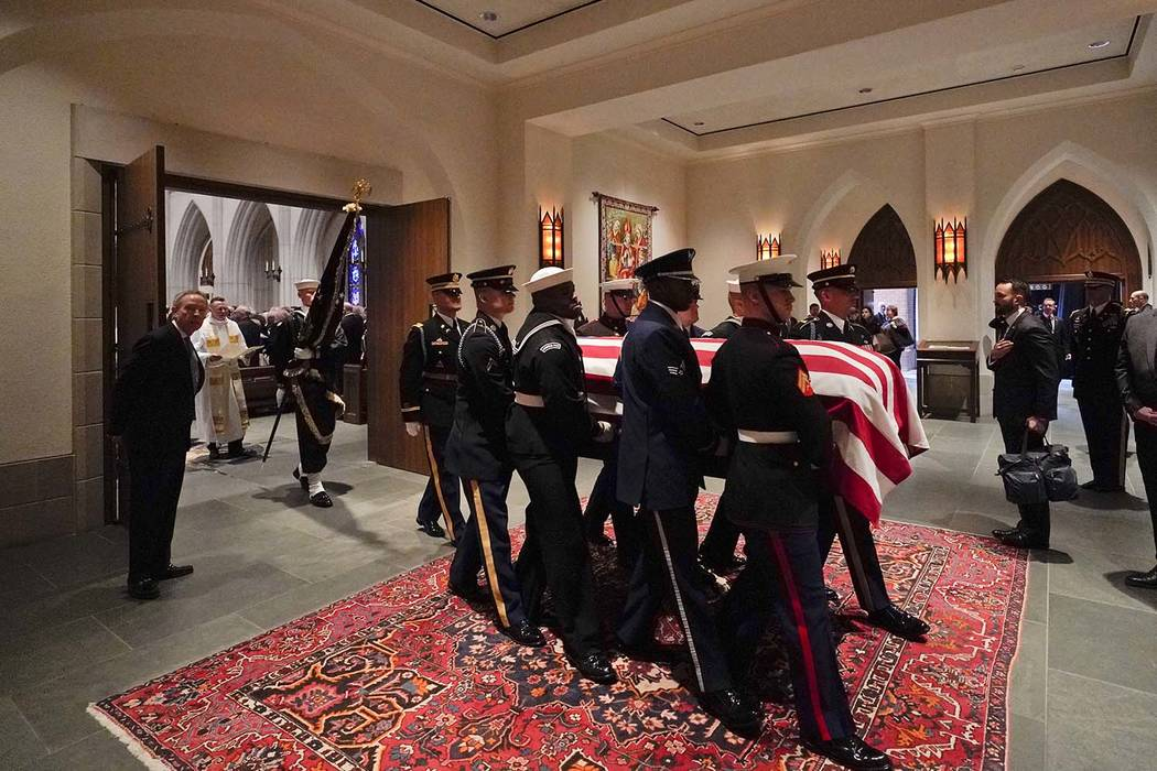A military honor guard carries the flag-draped casket of former President George H.W. Bush after a funeral at St. Martin's Episcopal Church Thursday, Dec. 6, 2018, in Houston. (AP Photo/David J. P ...
