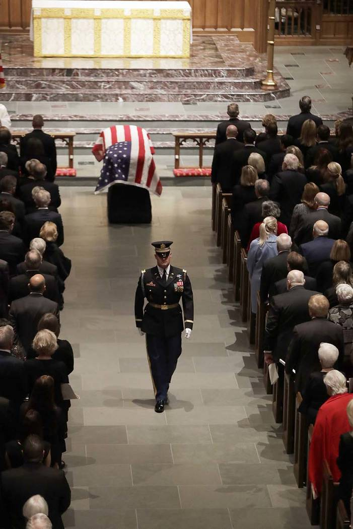 A member of the honor guard walks down the aisle after the flag-draped casket of former President George H.W. Bush was placed in St. Martin's Episcopal Church for his funeral Thursday, Dec. 6, 201 ...