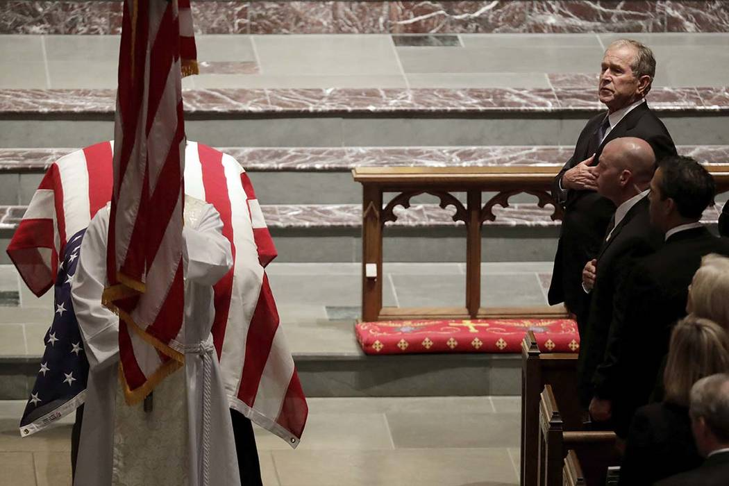 Former President George W. Bush places a hand on his chest during a funeral for former President George H.W. Bush at St. Martin's Episcopal Church Thursday, Dec. 6, 2018, in Houston. (AP Photo/Mar ...