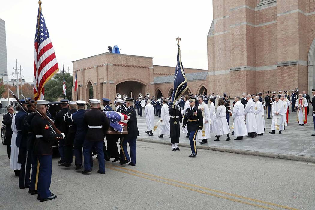 A military honor guard carries the flag-draped casket of former President George H.W. Bush to a hearse following his funeral service at St. Martin's Episcopal Church Thursday, Dec. 6, 2018, in Hou ...