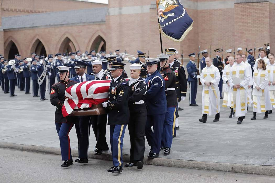 A military honor guard carries the flag-draped casket of former President George H.W. Bush from St. Martin's Episcopal Church following his funeral service Thursday, Dec. 6, 2018, in Houston. (AP ...