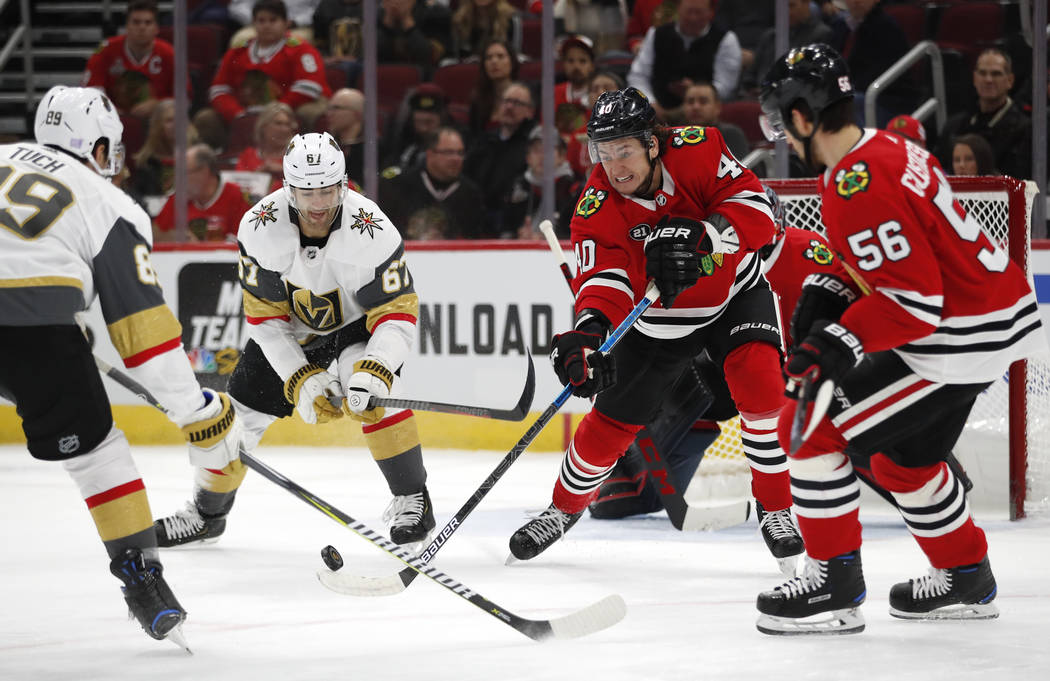 Chicago Blackhawks right wing John Hayden (40) clears the puck past Vegas Golden Knights right wing Alex Tuch (89) and left wing Max Pacioretty (67) as teammate Erik Gustafsson (56) look on during ...