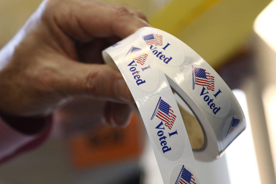 """Poll manager Larry Greer hands holds a roll of """"I Voted"""" stickers given each person after voting in a runoff election Tuesday, Nov. 27, 2018 in Ridgeland, Miss. Mississippi voters are d ..."""