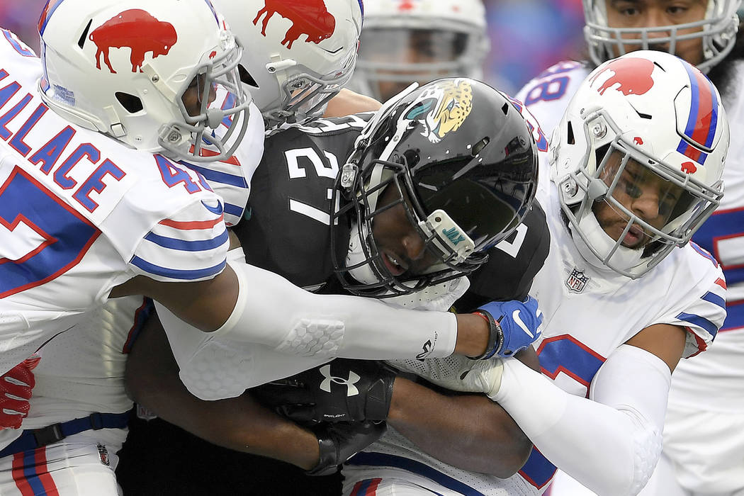 FILE - In this Nov. 25, 2018, file photo, Jacksonville Jaguars running back Leonard Fournette (27) is tackled by Buffalo Bills defenders during the first half of an NFL football gam in Orchard Par ...