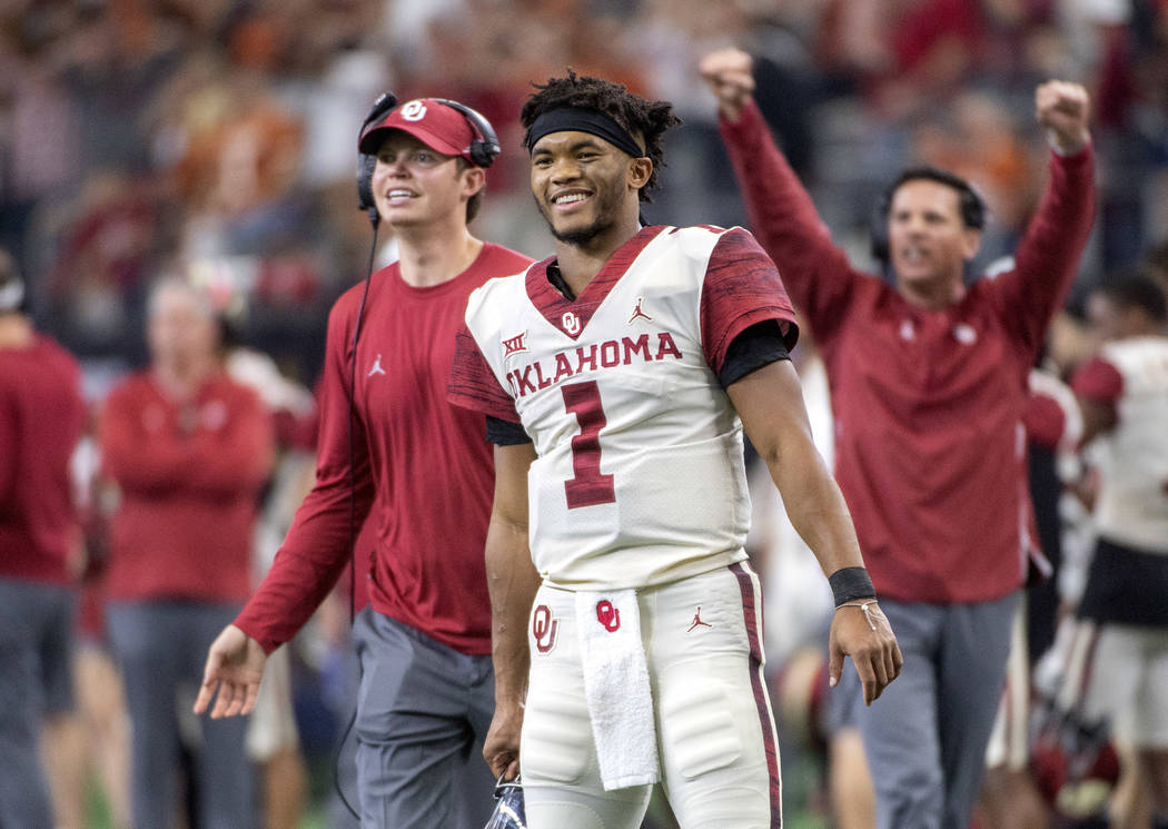 In this Dec. 1, 2018, file photo, Oklahoma quarterback Kyler Murray (1) celebrates on the sidelines after throwing a touchdown against Oklahoma during the second half of the Big 12 Conference cham ...
