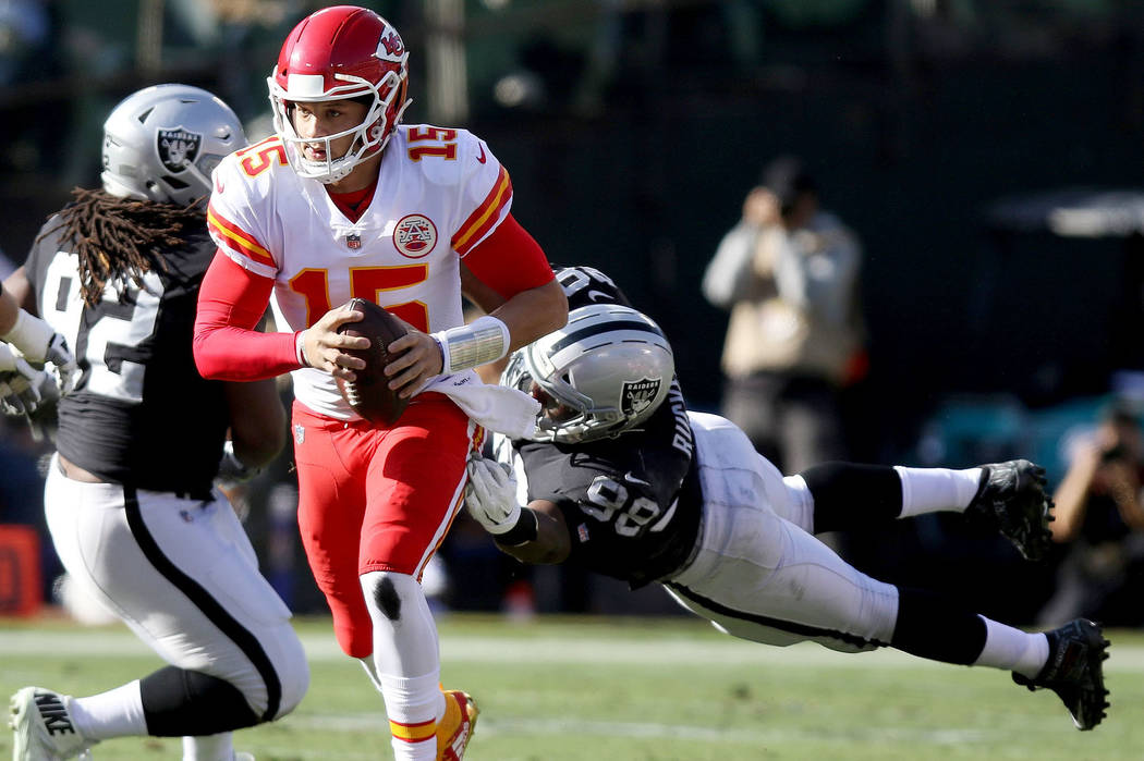 Kansas City Chiefs quarterback Patrick Mahomes (15) sheds tackle by Oakland Raiders defensive end Frostee Rucker (98) as Raiders defensive tackle P.J. Hall (92) and Chiefs offensive tackle Mitchel ...
