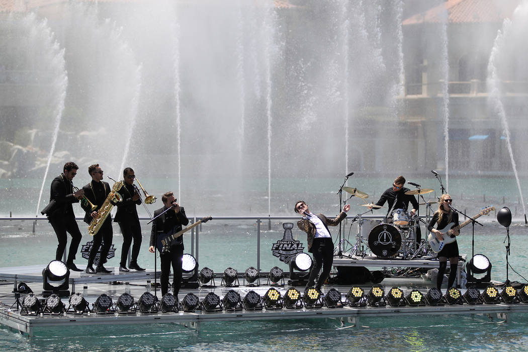 Frontman Brendon Urie, center, and members of the Las Vegas rock band Panic! at the Disco perform at the Fountains at Bellagio ahead of the Vegas Golden Knights-Washington Capitals NHL hockey game ...