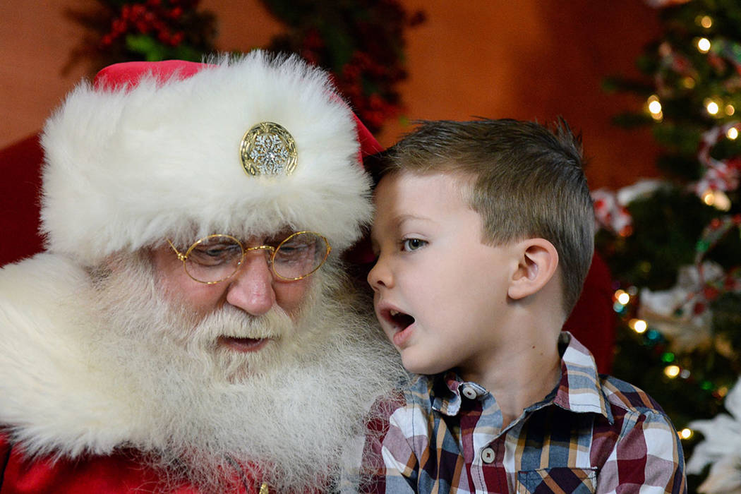 Maverick Willis, 5, from Henderson, whispers into John Jones' ear, dressed up as Santa Claus, as he tells him what he wants for Christmas at the District at Green Valley Ranch in Henderson, Saturd ...