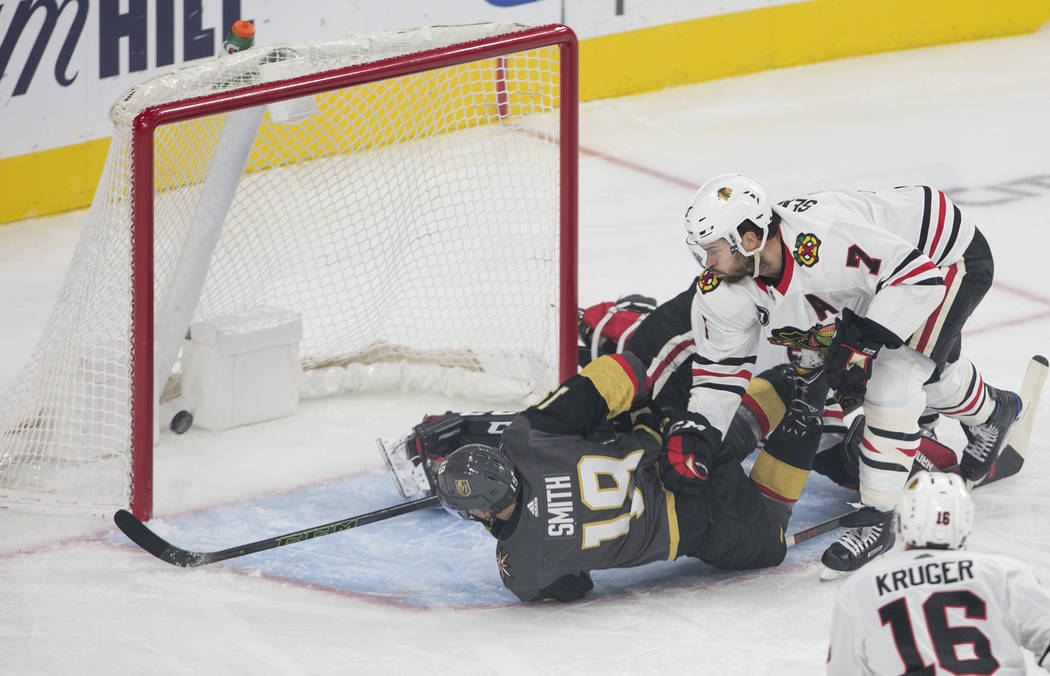 Vegas Golden Knights right wing Reilly Smith (19) falls to the ice as he scores a goal past Chicago Blackhawks defenseman Brent Seabrook (7) during the first period of an NHL hockey game at T-Mobi ...