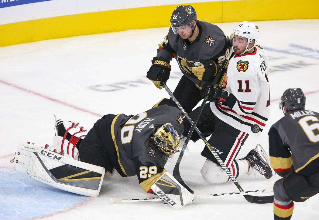 Vegas Golden Knights goaltender Marc-Andre Fleury (29) dives for the puck as Knights defenseman Nick Holden (22) collides with Chicago Blackhawks left wing Brendan Perlini (11) as they vie for pos ...