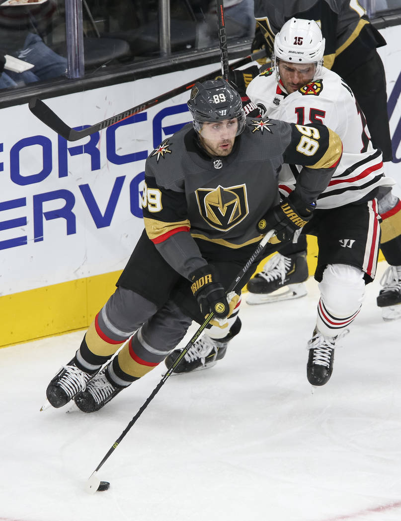 Vegas Golden Knights right wing Alex Tuch (89) carries the puck ahead of Chicago Blackhawks center Artem Anisimov (15) during the third period of an NHL hockey game at T-Mobile Arena in Las Vegas, ...