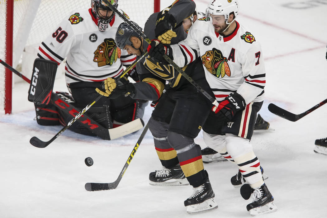 Vegas Golden Knights right wing Ryan Reaves (75) and Chicago Blackhawks defenseman Brent Seabrook (7) vie for the puck in front of Blackhawks goaltender Corey Crawford (50) during the first period ...