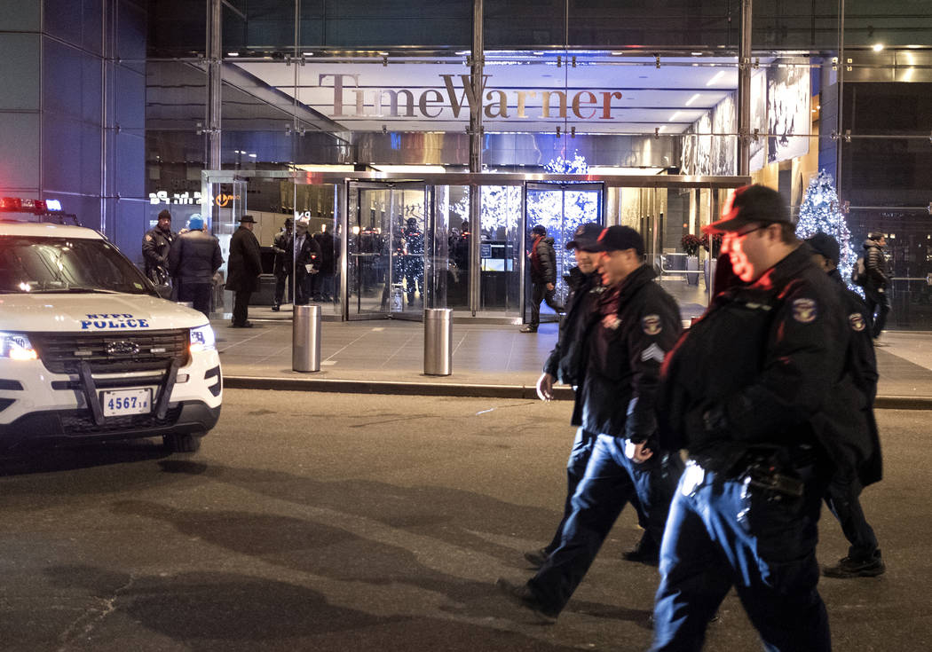 After the building was determined safe, New York City police officers walk from the area of Time Warner Center in New York Thursday, Dec. 6, 2018, after a bomb threat was called into the building ...