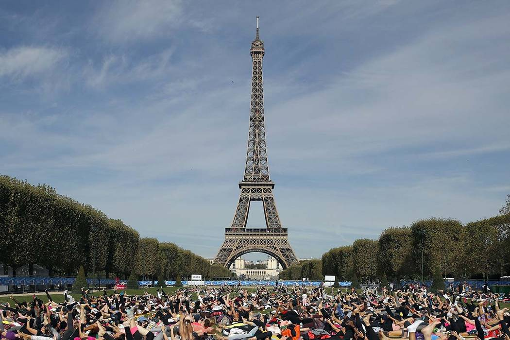 """In this Saturday, Sept. 8, 2018 file photo, participants perform yoga in front of the Eiffel Tower as part of the sport event """"La Parisienne"""", in Paris. The Eiffel Tower announces it will be close ..."""