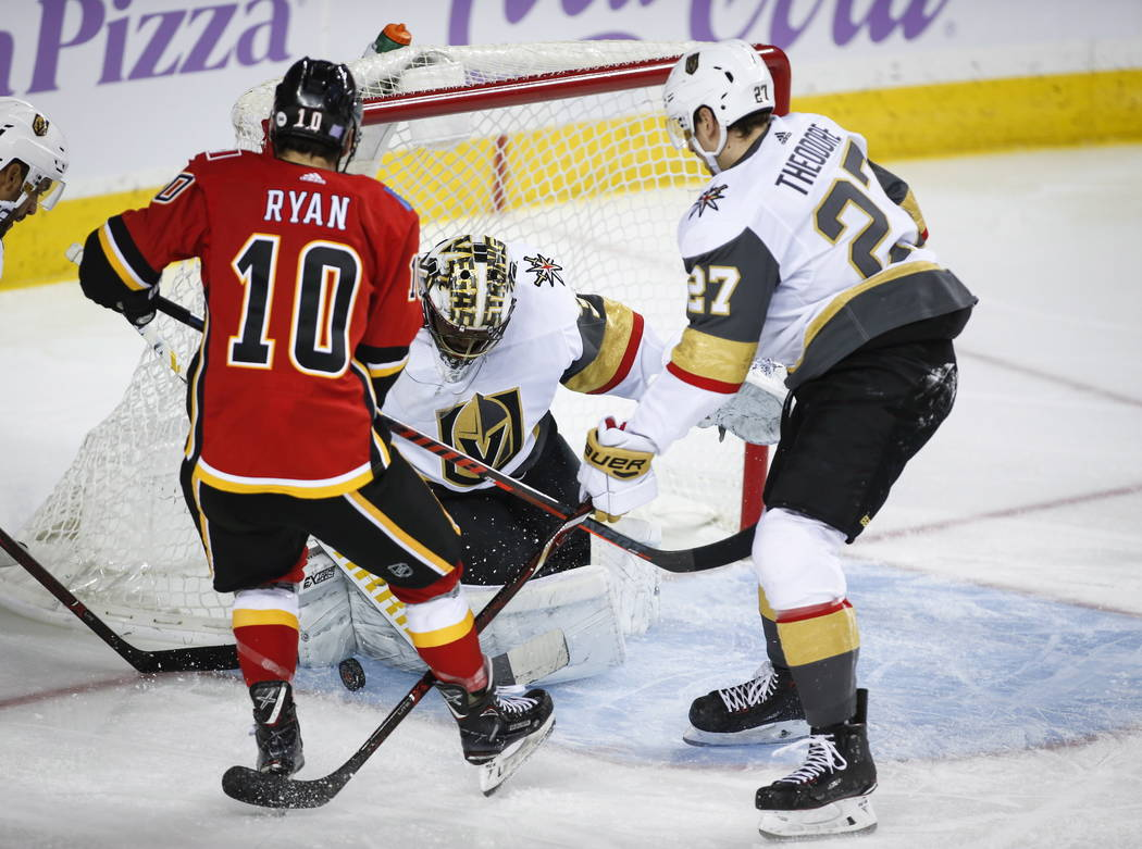 Vegas Golden Knights goalie Malcolm Subban, center, stops a shot from Calgary Flames' Derek Ryan, left, as Golden Knights' Shea Theodore looks on during first-period NHL hockey game action in Cal ...