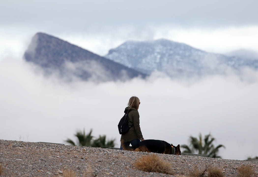A woman walks her dog as clouds loom over Red Rock Canyon on Friday, Dec. 7, 2018, in Las Vegas. Bizuayehu Tesfaye Las Vegas Review-Journal @bizutesfaye