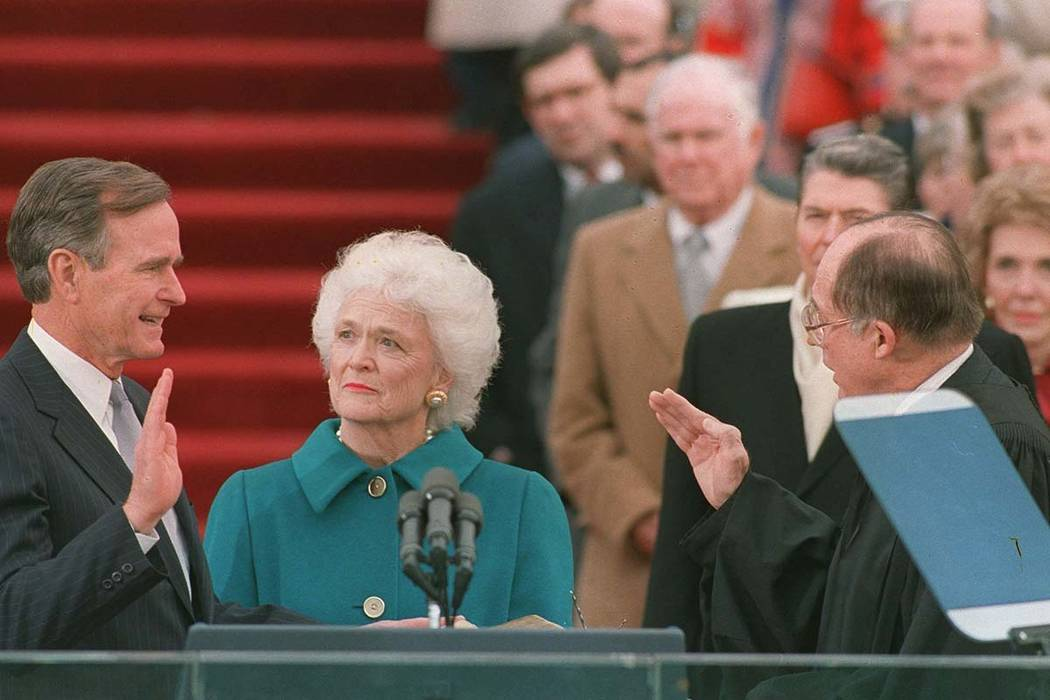 In this Jan. 20, 1989, file photo, President George H.W. Bush raises his right hand as he is sworn into office as the 41st president of the United States by Chief Justice William Rehnquist outside ...
