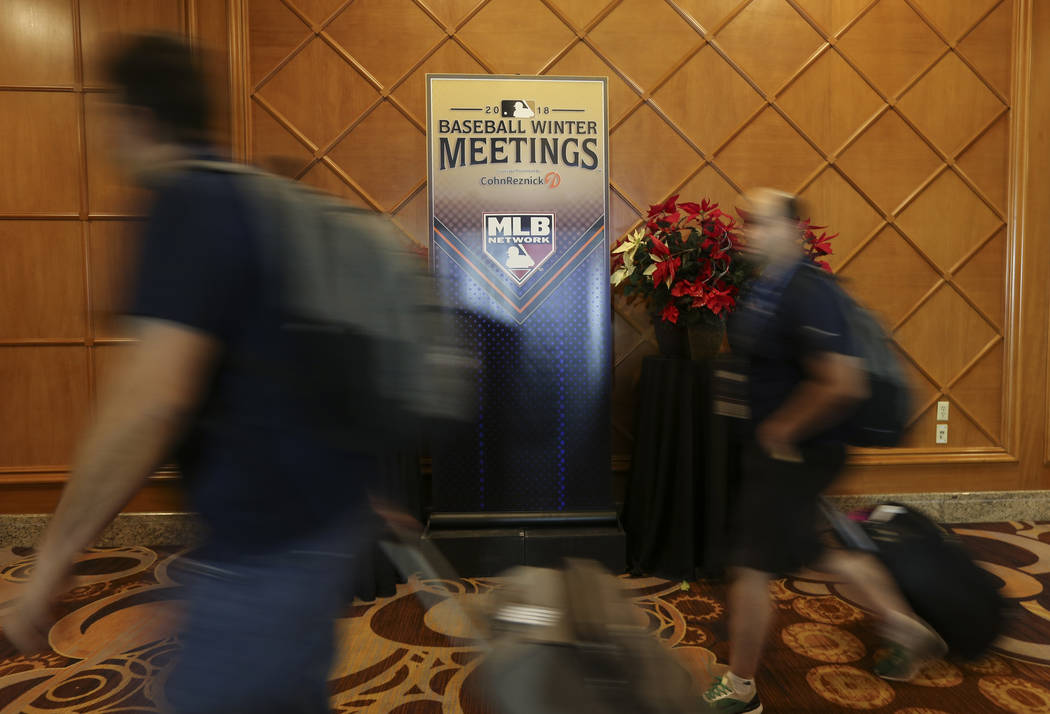 Attendees pass by signage for Major League Baseball's winter meetings at Mandalay Bay in Las Vegas on Sunday, Dec. 9, 2018. Chase Stevens Las Vegas Review-Journal @csstevensphoto