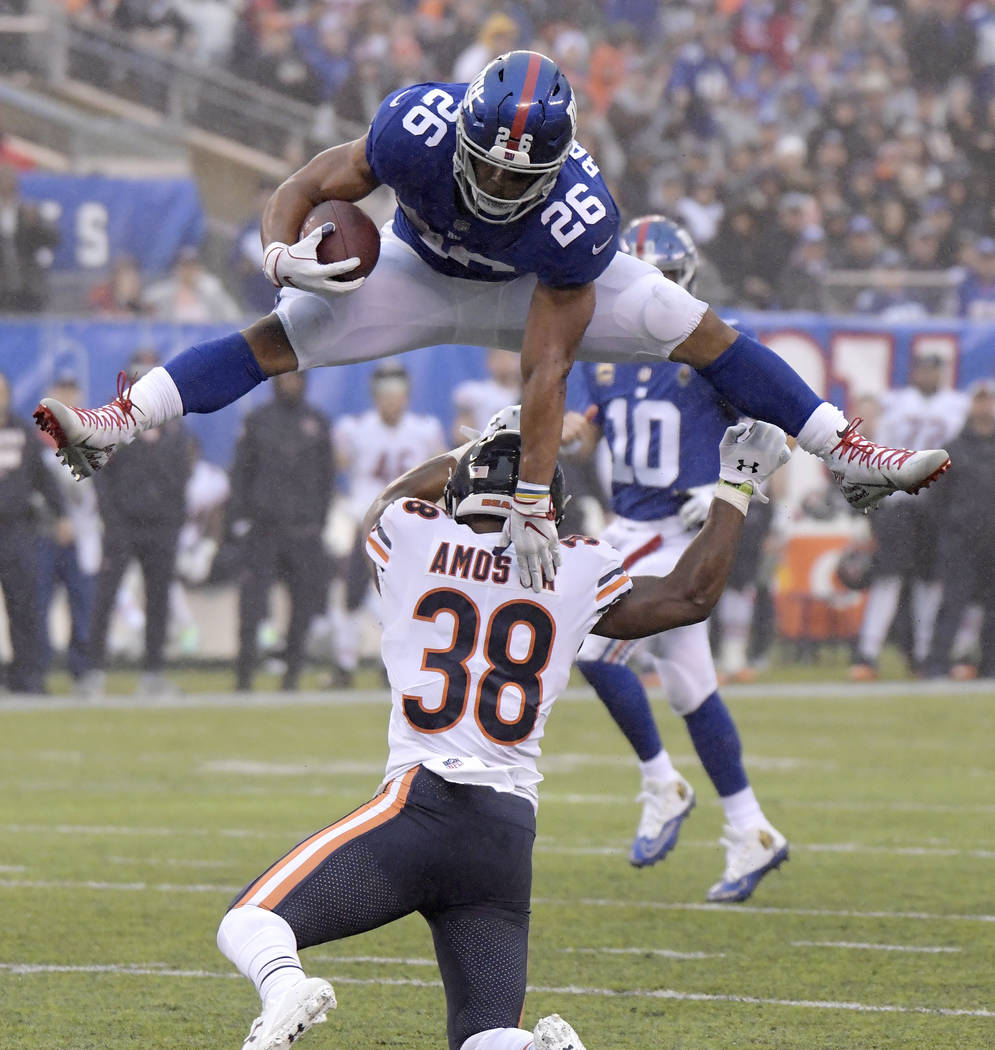 New York Giants running back Saquon Barkley (26) leaps over Chicago Bears strong safety Adrian Amos (38) during the second half of an NFL football game, Sunday, Dec. 2, 2018, in East Rutherford, N ...