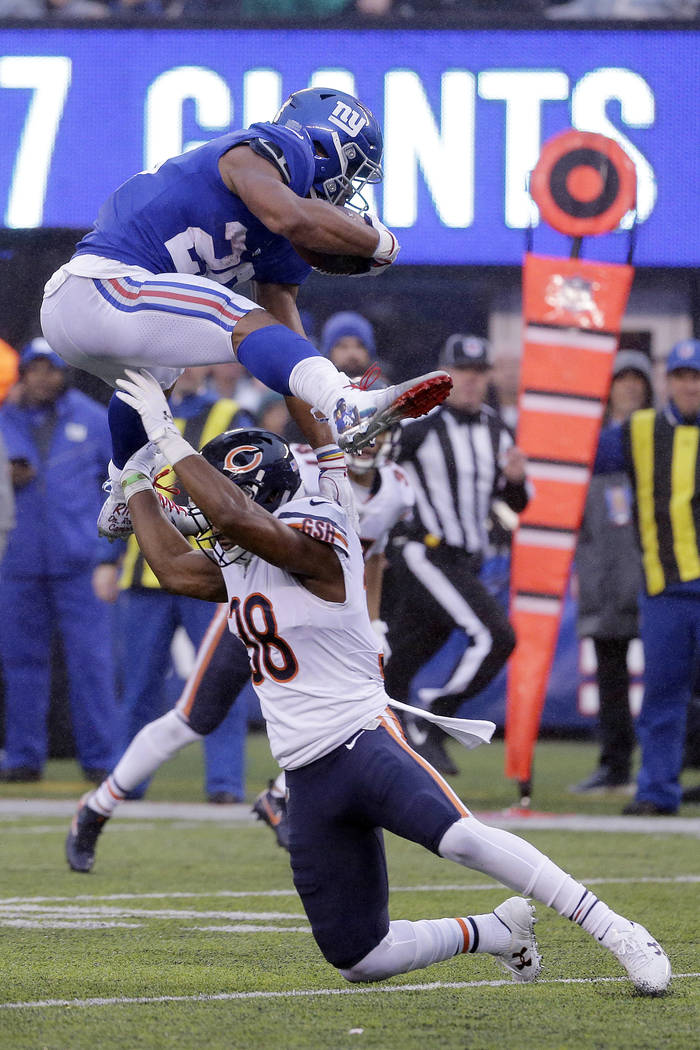 New York Giants running back Saquon Barkley, top, leaps over Chicago Bears strong safety Adrian Amos during the second half of an NFL football game, Sunday, Dec. 2, 2018, in East Rutherford, N.J. ...