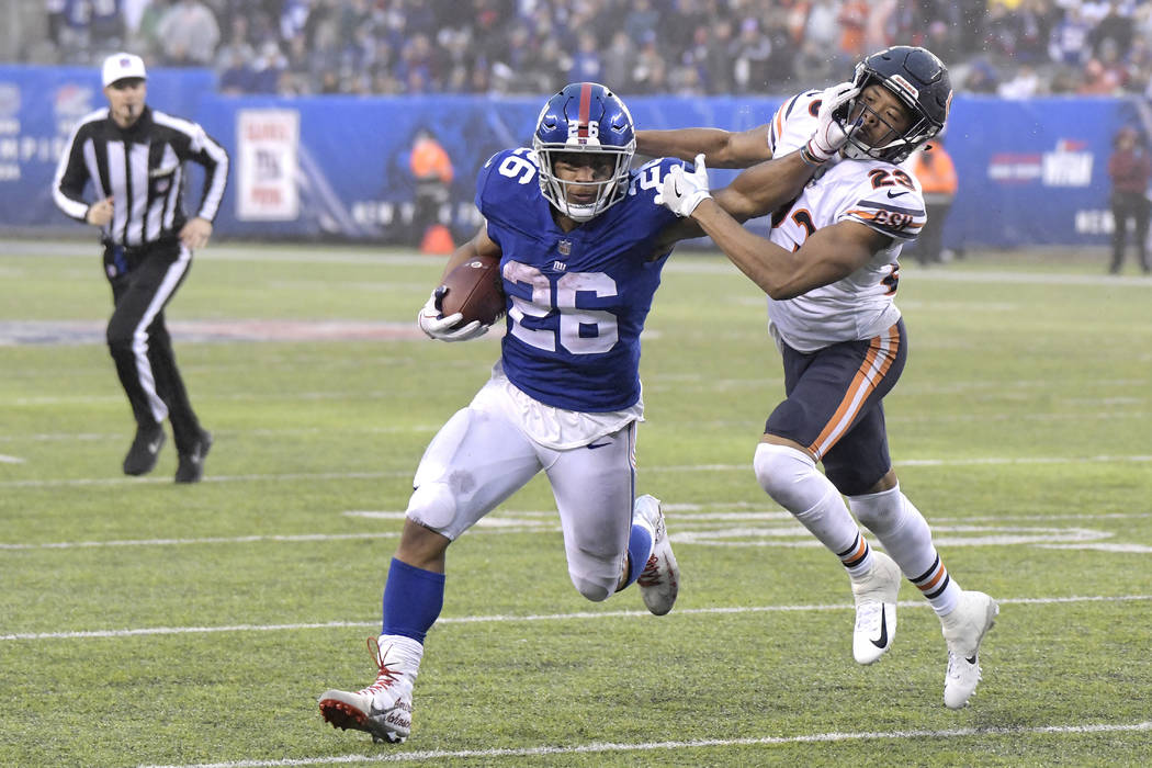 New York Giants running back Saquon Barkley (26) stiff arms Chicago Bears cornerback Kyle Fuller (23) during the second half of an NFL football game, Sunday, Dec. 2, 2018, in East Rutherford, N.J. ...