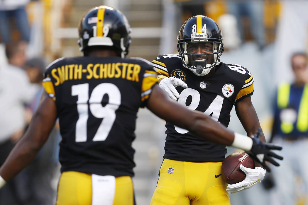 In this Oct. 22, 2017, file photo, Pittsburgh Steelers wide receiver Antonio Brown (84) celebrates with JuJu Smith-Schuster (19) afters scoring in the first half of an NFL football game against th ...