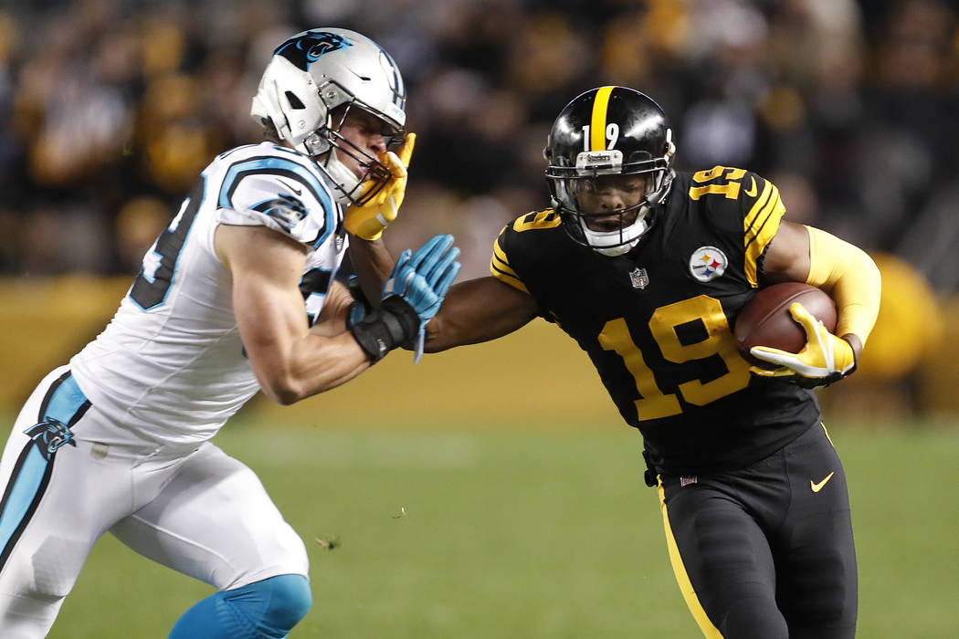 Pittsburgh Steelers wide receiver JuJu Smith-Schuster (19) tries to fend off Carolina Panthers free safety Mike Adams (29) during the first half of an NFL football game in Pittsburgh, Thursday, No ...
