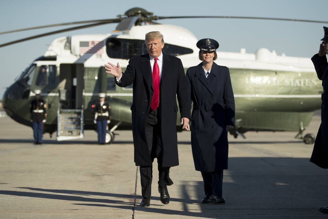 President Donald Trump walks to board Air Force One at Andrews Air Force Base, Md., Friday, Dec. 7, 2018, to travel to Kansas City, Mo., to speak at the 2018 Project Safe Neighborhoods National Co ...