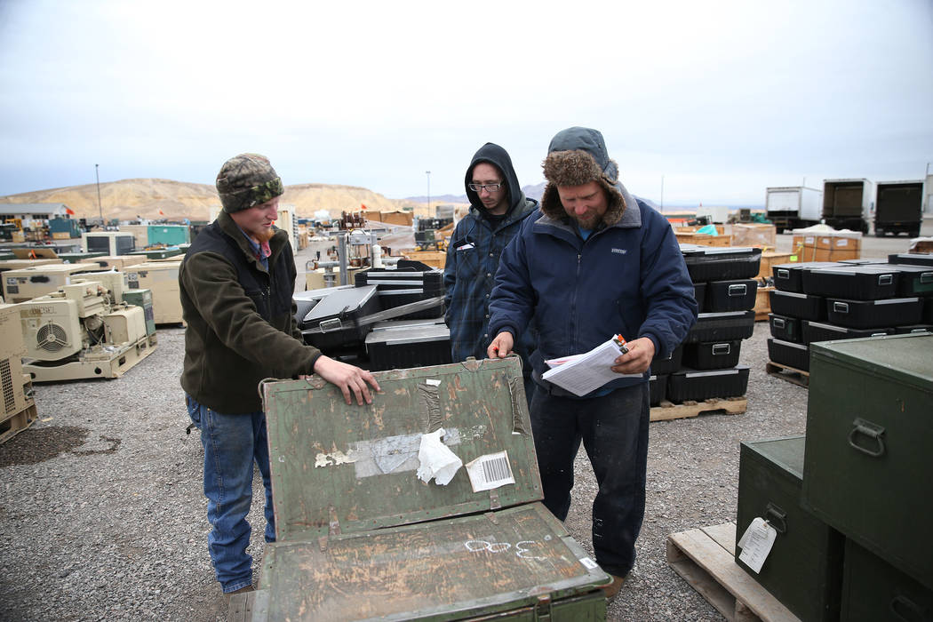 Utah residents Mason Fuller, from left, with friends Carson Collis and his father Carl Collis, browse military equipment for auction at the Ritchie Bros. auction house in Las Vegas, Thursday, Dec. ...