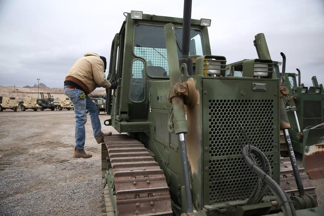 Danny Bee of California steps downs from a military bulldozer for auction at the Ritchie Bros. auction house in Las Vegas, Thursday, Dec. 6, 2018. Erik Verduzco Las Vegas Review-Journal @Erik_Verduzco