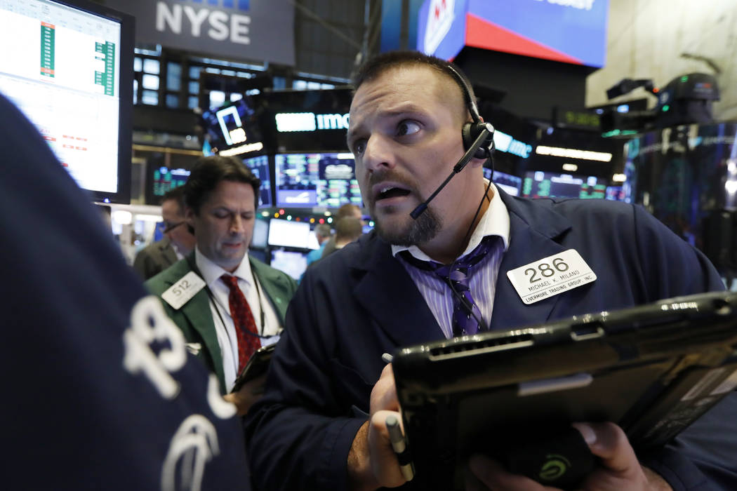 Trader Michael Milano, right, works on the floor of the New York Stock Exchange, Monday, Dec. 3, 2018. Wall Street ended a turbulent week of trading Friday, Dec. 7, with the biggest weekly loss si ...