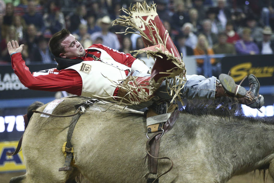 "Shane O'Connell of Rapid City, S.D. rides ""Night Fist"" while competing in bareback riding during the opening night of the National Finals Rodeo at the Thomas & Mack Center in Las Veg ..."