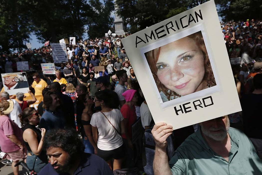 "A counter-protester holds a photo of Heather Heyer on Boston Common at a ""Free Speech"" rally organized by conservative activists in Boston, Aug. 19, 2017. (Michael Dwyer/AP file)"