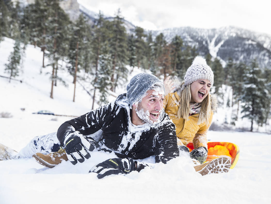 Dominic Marchese, left, and Dani Hernandez share a laugh after crashing their sled at Lee Meadows on Friday, Nov. 30, 2018, outside Lee Canyon, in Las Vegas. Benjamin Hager Las Vegas Review-Journal
