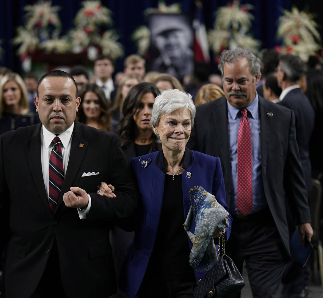Jerry Reyes, with the Geo. H. Lewis & Sons funeral home, escorts widow Janice McNair, followed by her son Cal McNair, after a public celebration of life for Houston Texans owner Robert C. McNa ...