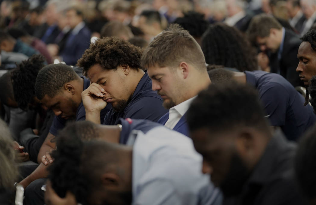 Houston Texans players bow their heads during a prayer at a public celebration of life for Houston Texans owner Robert C. McNair at NRG Stadium, Friday, Dec. 7, 2018, in Houston. McNair, who broug ...