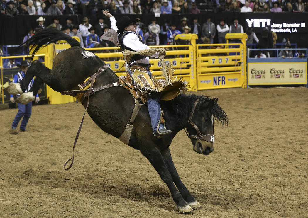 """Joey Sonnier, of New Iberia, La., rides """"Happy Valley"""" while competing in saddle bronc riding during the second go-round of the National Finals Rodeo at the Thomas & Mack Center in L ..."""