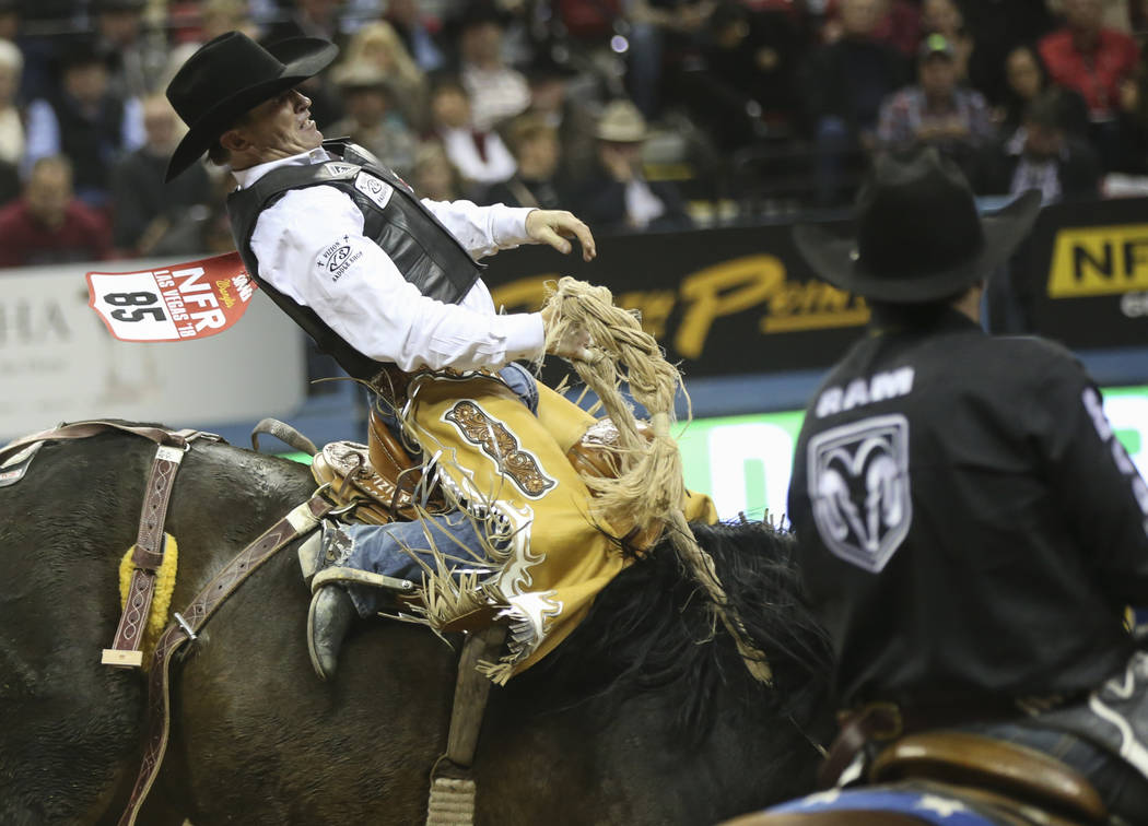 "Joey Sonnier, of New Iberia, La., rides ""Happy Valley"" while competing in saddle bronc riding during the second go-round of the National Finals Rodeo at the Thomas & Mack Center in L ..."
