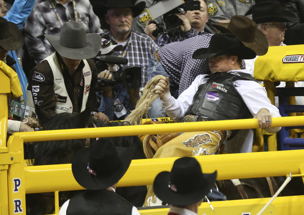 """Joey Sonnier, of New Iberia, La., prepares to ride """"Happy Valley"""" in the saddle bronc riding during the second go-round of the National Finals Rodeo at the Thomas & Mack Center in La ..."""