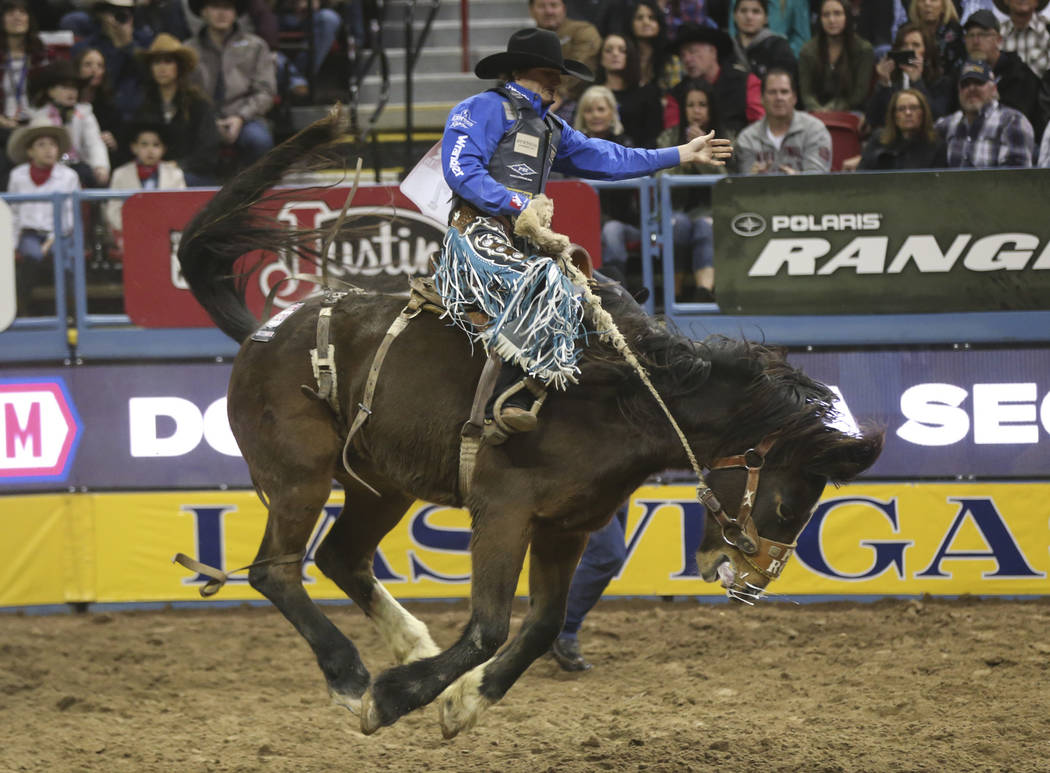 """Cort Scheer, of Elsmere, Neb., rides """"Larry Cuipepper"""" while competing in saddle bronc riding during the second go-round of the National Finals Rodeo at the Thomas & Mack Center in L ..."""