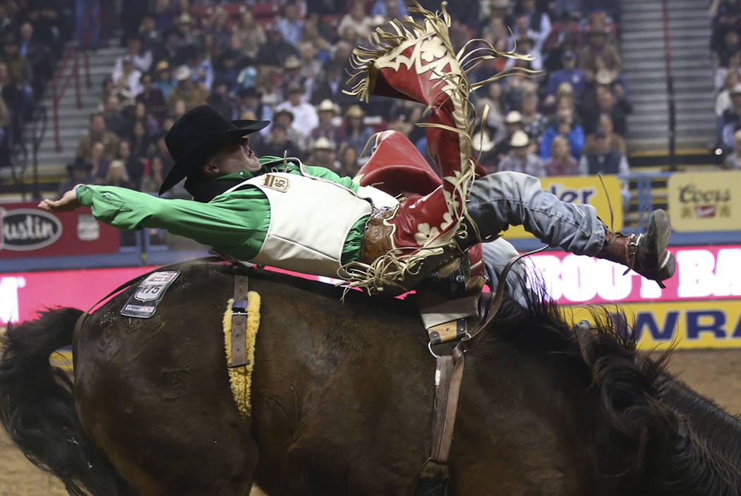 """Shane O'Connell, of Rapid City, S.D., rides """"Scarlet Fever"""" while competing in bareback riding during the second go-round of the National Finals Rodeo at the Thomas & Mack Center in ..."""