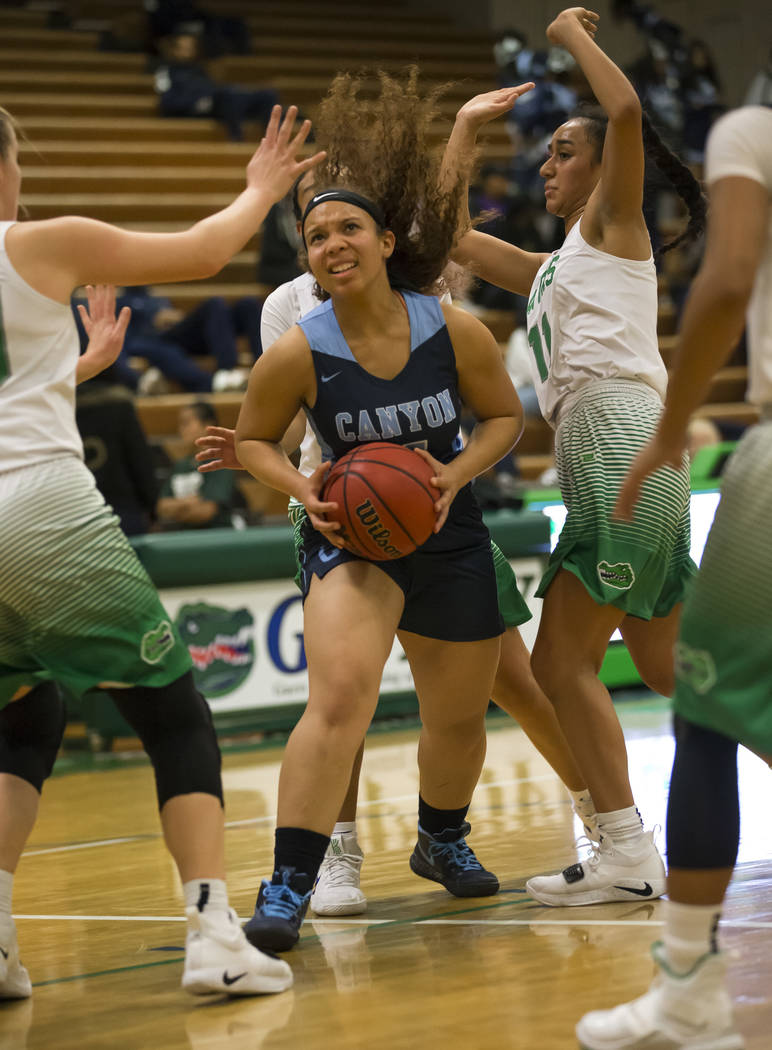 Canyon Springs guard J'hane Richardson (4) drives the ball through Green Valley's Julia Clark (10), left, and Lusi Soifua (11) during the first half of a varsity basketball game at Green Valley Hi ...